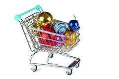 Carretilla de las compras con las decoraciones de la Navidad aisladas en blanco Imagen de archivo