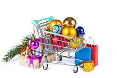 Carretilla de las compras con las decoraciones de la Navidad y cajas con los regalos Fotografía de archivo libre de regalías