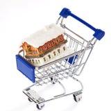 Carretilla de las compras con la casa aislada Fotografía de archivo