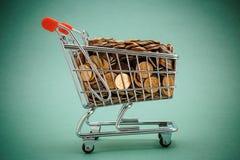 Carretilla de las compras con las monedas Imágenes de archivo libres de regalías
