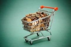 Carretilla de las compras con las monedas Imagenes de archivo