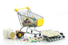 Carretilla de las compras con las píldoras aisladas en el fondo blanco Imágenes de archivo libres de regalías