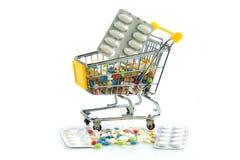 Carretilla de las compras con las píldoras aisladas en el fondo blanco Foto de archivo