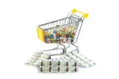 Carretilla de las compras con las píldoras aisladas en el fondo blanco Fotografía de archivo libre de regalías