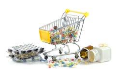 Carretilla de las compras con las píldoras aisladas en la farmacia blanca del fondo Imagen de archivo libre de regalías