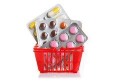 Carretilla de las compras con las píldoras y medicina aislada en blanco Foto de archivo libre de regalías