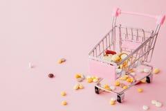 Carretilla de las compras del supermercado por completo de píldoras y de drogas en un fondo rosado Compras de las preparaciones m foto de archivo