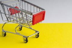 Carretilla de las compras en fondo colorido fotografía de archivo