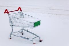 Carretilla de las compras en la nieve Imagen de archivo libre de regalías