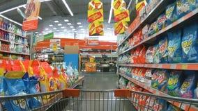Carretilla de las compras que se mueve entre los estantes con los detergentes en el supermarke almacen de metraje de vídeo