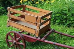 Carretilla de madera antigua con las ruedas rojas imagen de archivo libre de regalías