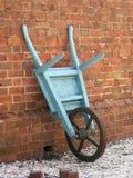 Carretilla de rueda antigua contra ladrillo Imagenes de archivo