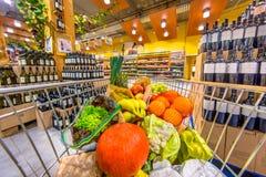 Carretilla del supermercado con la fruta y verdura en la sección del alcohol imagen de archivo libre de regalías