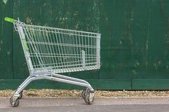 Carretilla del supermercado en el fondo de una cerca verde Carro del supermercado en el pavimento foto de archivo libre de regalías