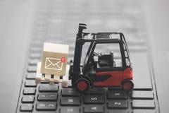Carretilla elevadora con el nuevo gráfico del correo electrónico en bloque de madera sobre el teclado del ordenador portátil Imagen de archivo