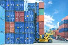 Carretilla elevadora que maneja la caja del envase que carga al camión en zona logística de las importaciones/exportaciones Fotografía de archivo