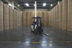 Carretilla elevadora y Rolls enorme del papel en fábrica Foto de archivo libre de regalías