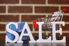 Carretilla para los productos en una venta del ` s del Año Nuevo del fondo de la pared de ladrillo Fotografía de archivo