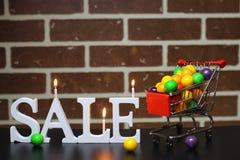 Carretilla para los productos en una venta del ` s del Año Nuevo del fondo de la pared de ladrillo Foto de archivo