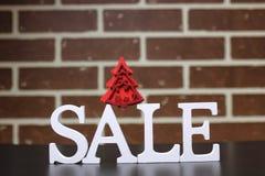 Carretilla para los productos en una venta del ` s del Año Nuevo del fondo de la pared de ladrillo Imagenes de archivo