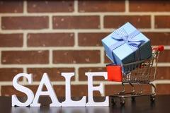Carretilla para los productos en una venta del ` s del Año Nuevo del fondo de la pared de ladrillo Fotos de archivo