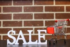 Carretilla para los productos en una venta del ` s del Año Nuevo del fondo de la pared de ladrillo Fotos de archivo libres de regalías