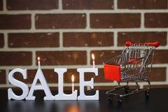 Carretilla para los productos en una venta del ` s del Año Nuevo del fondo de la pared de ladrillo Imagen de archivo