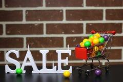 Carretilla para los productos en una venta del ` s del Año Nuevo del fondo de la pared de ladrillo Imagen de archivo libre de regalías