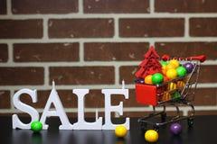 Carretilla para los productos en una venta del ` s del Año Nuevo del fondo de la pared de ladrillo Imágenes de archivo libres de regalías