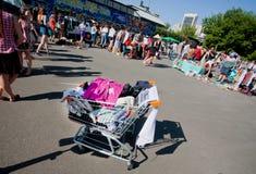 Carretilla por completo de la ropa en el mercado de pulgas de la calle Foto de archivo