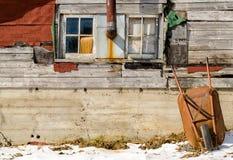 Carretilla que descansa sobre una pared de madera de la casa vieja colorida en invierno Fotos de archivo