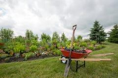 Carretilla roja con la pala en el jardín Imágenes de archivo libres de regalías