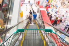 Carretilla vacía de las compras en la escalera móvil en alameda de compras Foto de archivo