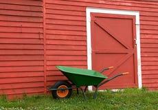 Carretilla verde, granero rojo imagen de archivo libre de regalías