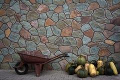 Carretilla y calabazas cerca de la pared de piedra fotografía de archivo