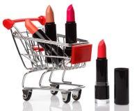 Carretilla y lápices labiales de las compras aislados Fotos de archivo