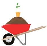 Carretilla y planta de semillero Imágenes de archivo libres de regalías