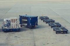 Carretillas para los envases del equipaje en el campo de aviación foto de archivo