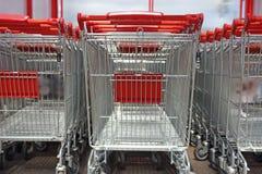 Carretillas que hacen compras con las manijas rojas que se colocan en fila Compras co Fotografía de archivo libre de regalías