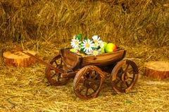Carretto decorativo con i fiori sul fieno fotografia stock libera da diritti