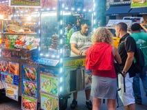 Carretto degli alimenti a rapida preparazione al quinto viale in New York alla notte Immagine Stock