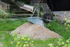 Carretto della costruzione capovolto sul mucchio della sabbia Immagine Stock