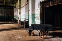 Carretto di legno antico con le ruote del ghisa - fabbrica di vetro abbandonata della mano fotografie stock