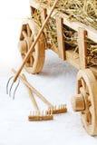 Carretto di legno del fieno su un fondo bianco Forcelle e rastrelli Fotografie Stock