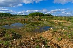 Carrière abandonnée, ciel bleu et nuages blancs Image stock