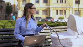 Carrière vrouwelijke werkende laptop en slingerende zuigeling in kinderwagenzitting op parkbank stock videobeelden