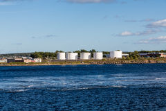 Carri armati dell'olio bianco tecnico sulla costa della baia blu Fotografia Stock Libera da Diritti