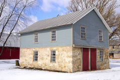 Carriage barn. 19th century carriage barn features stone base and clapboard construction fits snuggly into a classic farm settlement pattern Stock Images