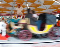 Carriage on carousel in movement. Afternoon at the playground games with the family Stock Image