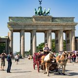 Coachman with horse-drawn carriage at Brandenburg Gate, Berlin, Brandenburger Tor. Carriage driver in front of the Brandenburger Tor - Brandenburg Gate on the royalty free stock photography